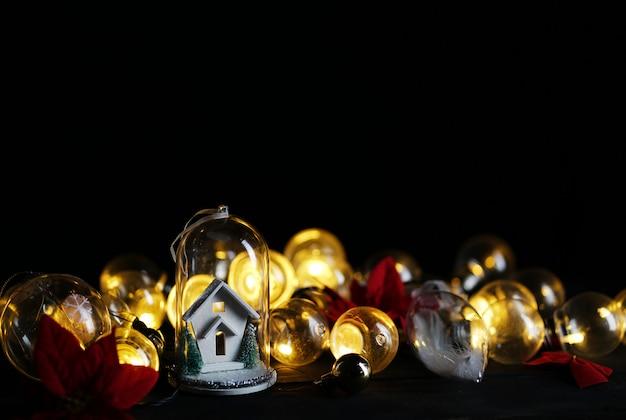 Casa branca da decoração do natal dentro do vidro entre o bulbo de luzes e a poinsétia vermelha. quarto para texto