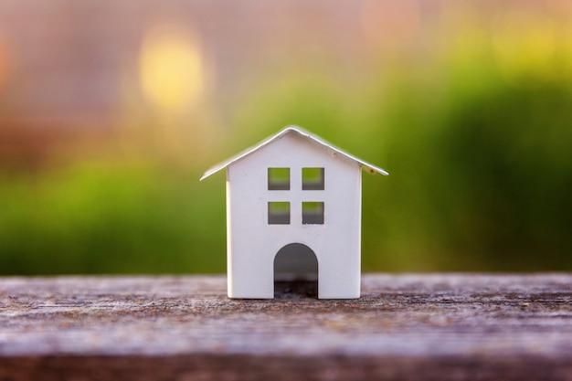 Casa branca diminuta do modelo do brinquedo na parede de madeira perto do contexto verde. eco village, parede ambiental abstrata