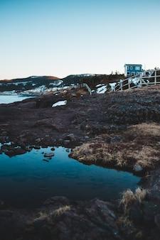 Casa branca e azul no campo marrom e grama perto do corpo de água durante o dia