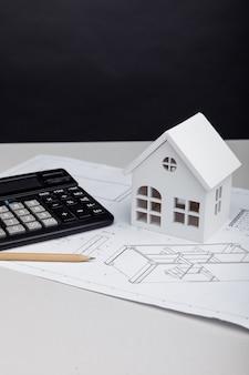 Casa branca e calculadora no projeto arquitetônico. conceito de custos de construção de casa. imagem vertical