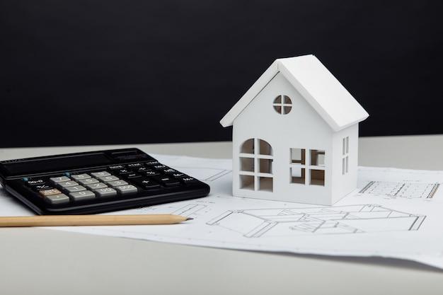 Casa branca e calculadora no projeto arquitetônico. conceito de custos de construção de casas