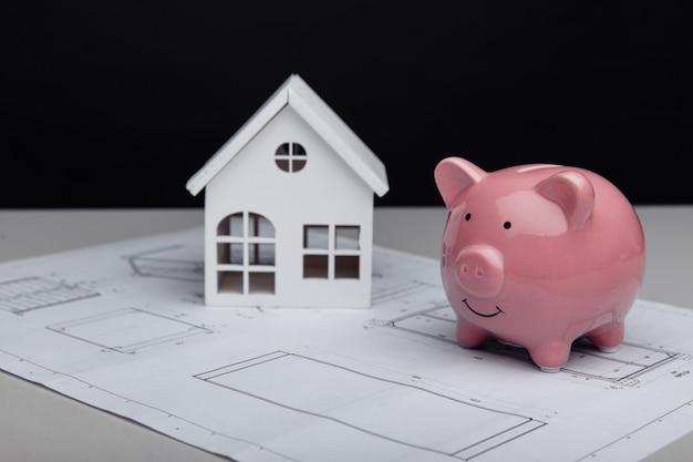 Casa branca e cofrinho com custos de construção da casa no plano arquitetônico
