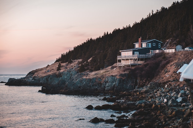 Casa branca e marrom na montanha rochosa marrom ao lado do corpo de água durante o dia