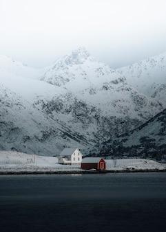 Casa branca e uma cabana vermelha à beira do lago no inverno