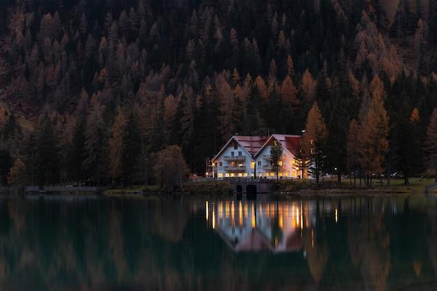 Casa branca e vermelha, cercada por árvores à noite