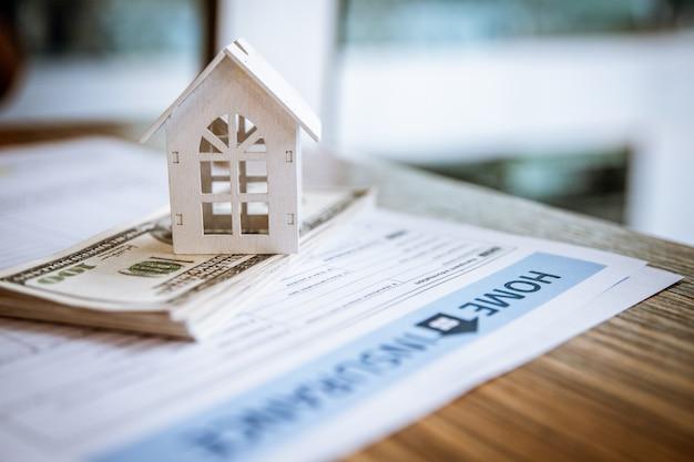 Casa branca modelo na nota de banco do dólar. conceito de seguros e imobiliário de investimento imobiliário.