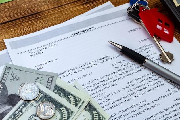 Casa, casa, propriedade, arrendamento imobiliário contrato contrato caneta dinheiro moedas chaves fundo de madeira, despesas, compra, investimento, finanças, poupança, conceito close-up
