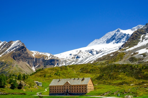Casa cercada por montanhas rochosas cobertas de vegetação e neve em valais, na suíça