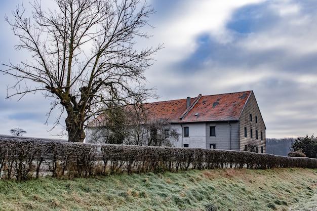 Casa cercada por vegetação com colinas sob um céu nublado ao fundo