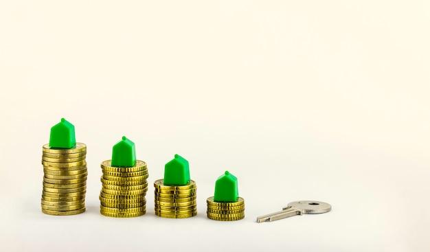 Casa chave e mini casas sobre as moedas, investimento imobiliário, economizar dinheiro com moedas de pilha