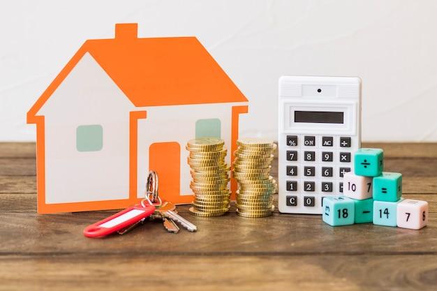 Casa, chave, moedas empilhadas, calculadora e blocos de matemática na mesa de madeira