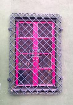 Casa cinza com moldura de janela rosa e barras roxas em estilo vintage