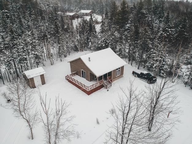 Casa coberta de neve, cercada por árvores