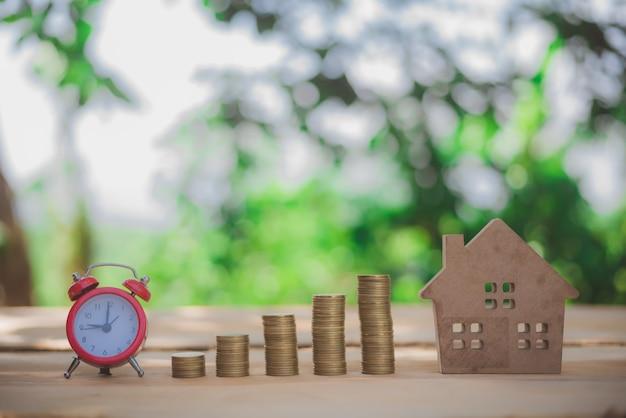 Casa colocada em moedas mão de homens está planejando dinheiro de poupança de moedas