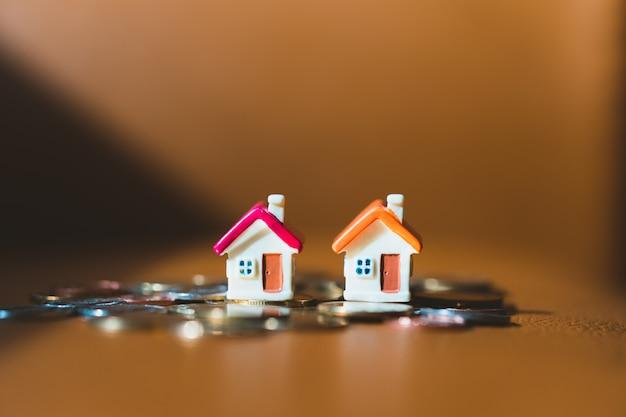 Casa colorida em miniatura na pilha moedas usando como propriedade e conceito de negócio