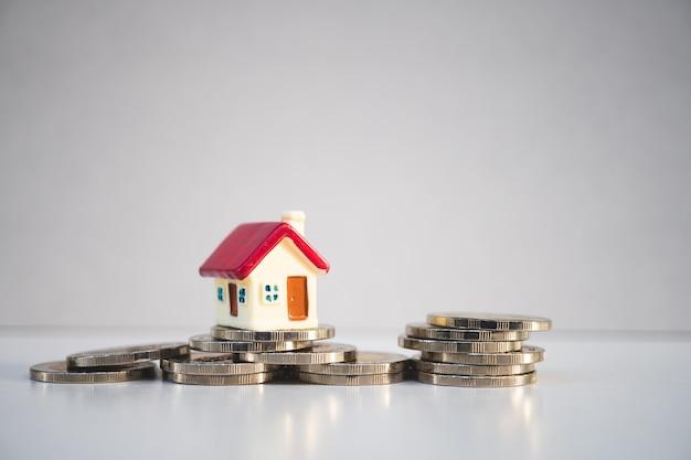 Casa colorida em miniatura na pilha moedas usando como propriedade e conceito financeiro