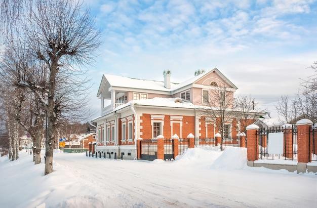 Casa com mezanino na margem do rio volga em plyos na neve sob a luz do sol de inverno