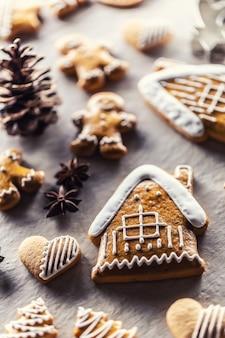 Casa com pão de gengibre e outros biscoitos de natal, juntamente com canela e pinhas.