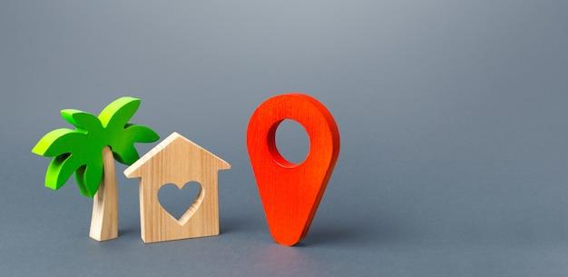 Casa com um coração e um pino indicador de navegação vermelho. escolhendo um lugar para uma viagem romântica