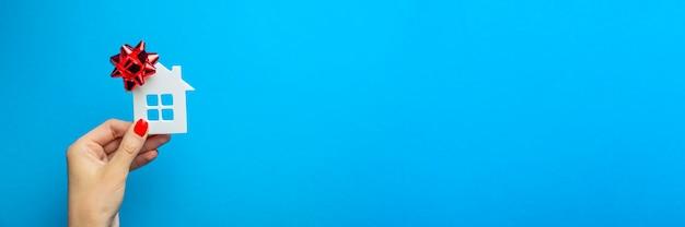 Casa como um presente. casa de brinquedo com um laço de presente na mão. conceito de presente imobiliário sobre fundo azul. cartão postal para impressão, banner com lugar para texto.