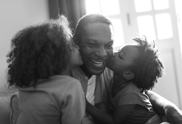 Casa da família de ascendência africana, crianças beijando seu pai