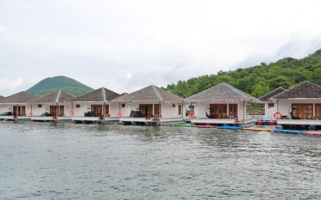 Casa da jangada que flutua no rio com a montanha no kanchanaburi, recurso em tailândia.