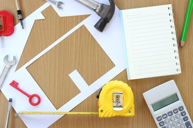 Casa dada forma de papel em um fundo da ferramenta marrom da madeira e do artesão.