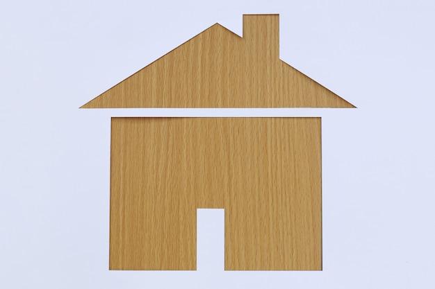 Casa dada forma papel em um fundo da madeira marrom.