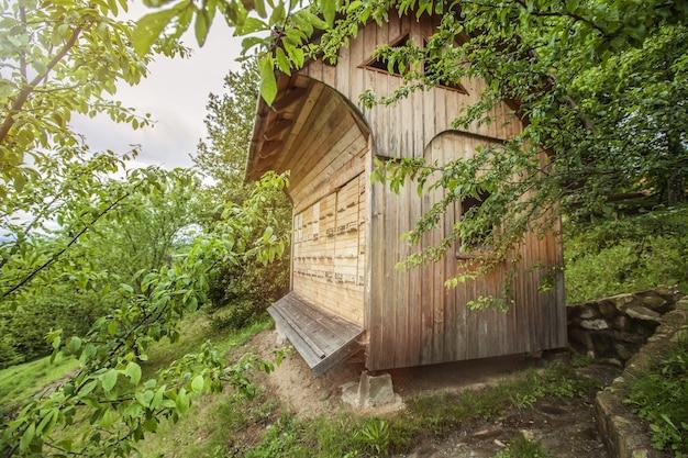 Casa de abelhas de madeira cercada por árvores no campo