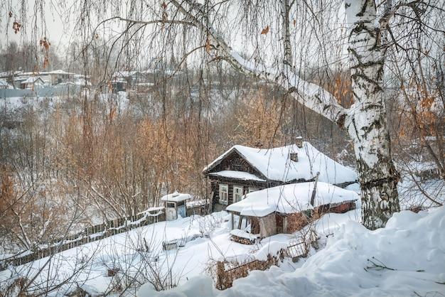 Casa de aldeia de madeira em um dia ensolarado de inverno com neve