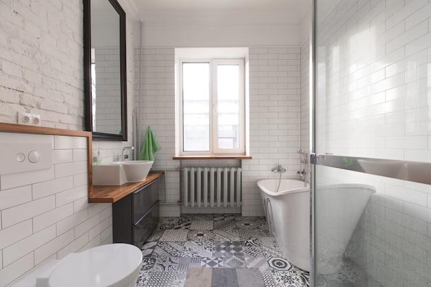 Casa de banho branca bonita no sótão em cinza pastel e nu cores, com banho oval espectacular