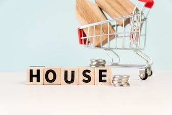Casa de blocos de madeira com pilha de moedas na frente do modelo de casa no carrinho de compras