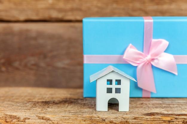 Casa de brinquedo branca em miniatura e caixa de presente embrulhada em papel azul em fundo de madeira