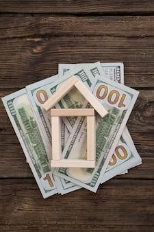 Casa de brinquedo de madeira com dólares em fundo de madeira velho