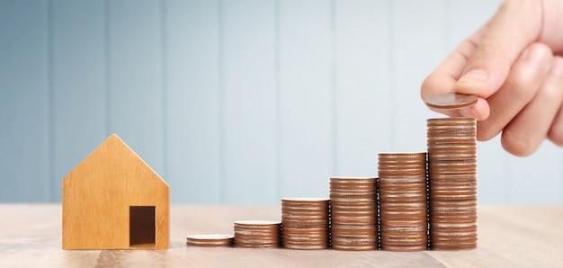 Casa de brinquedo de madeira conceito de casa de propriedade de hipoteca comprando para a família, moedas na mão