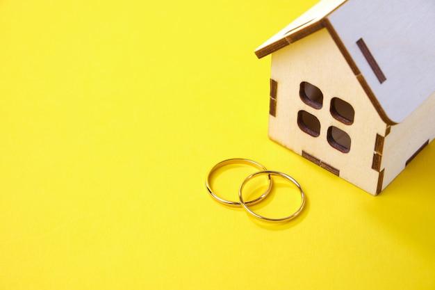 Casa de brinquedo de madeira e alianças de casamento em um fundo amarelo