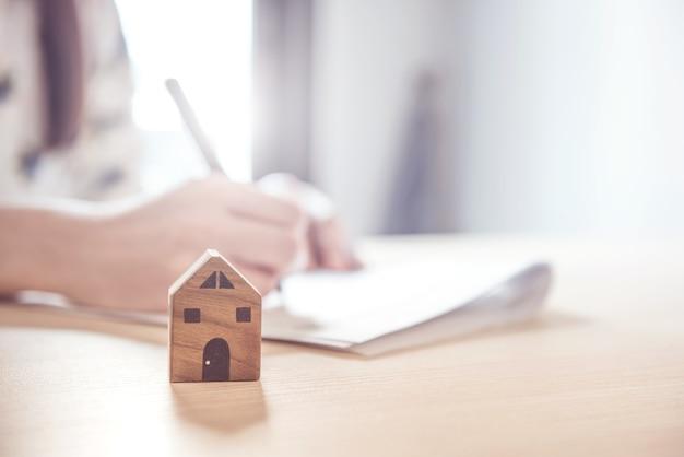 Casa de brinquedo de madeira perto com mulher assina um contrato de compra ou hipoteca para uma casa