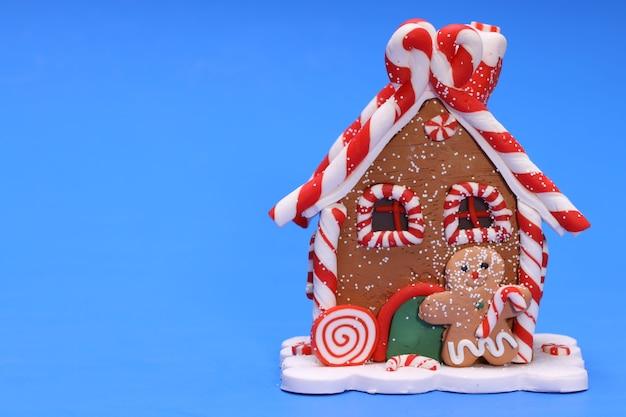 Casa de brinquedo de natal com o homem-biscoito em fundo azul