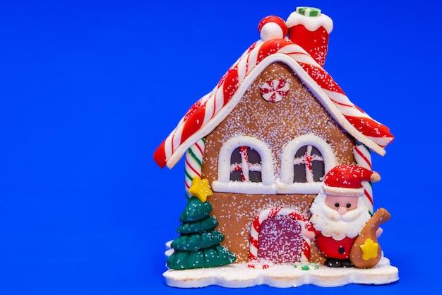 Casa de brinquedo de natal com papai noel em um fundo azul