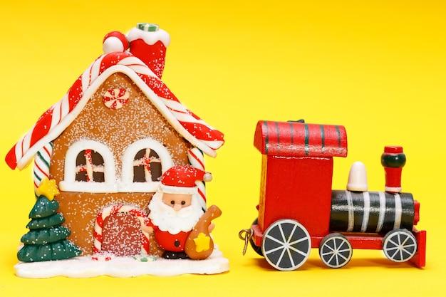 Casa de brinquedo de natal com trem de papai noel em um fundo amarelo