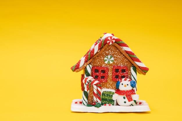 Casa de brinquedo de natal com um boneco de neve em um fundo amarelo