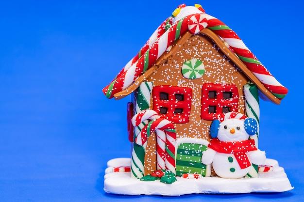 Casa de brinquedo de natal com um boneco de neve em um fundo azul