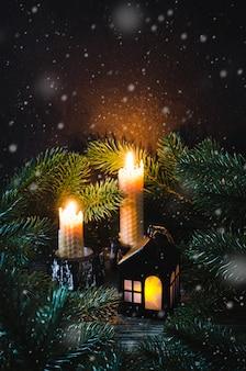 Casa de brinquedo de natal e duas velas entre o abeto.