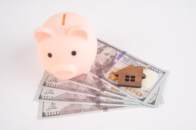 Casa de brinquedo e cofrinho de porco em notas de dólar americano em fundo branco.