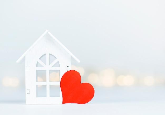 Casa de brinquedo e dia dos namorados em forma de coração na parede desfocada