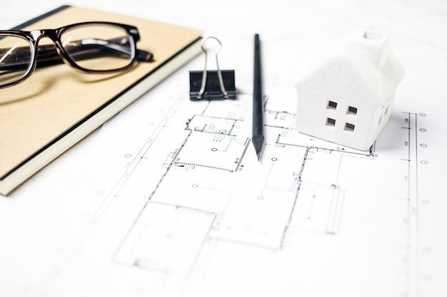 Casa de brinquedo e óculos perto de papelaria e blueprint