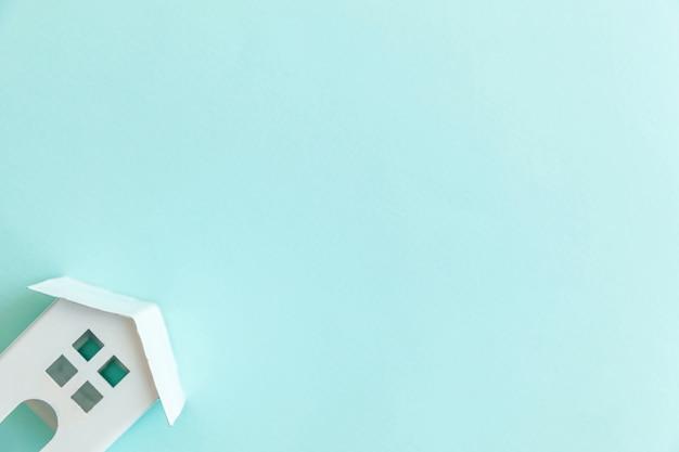 Casa de brinquedo em miniatura branca sobre fundo azul pastel