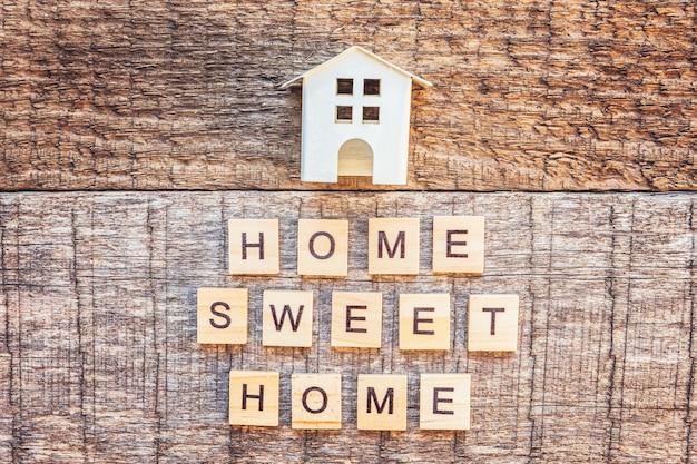 Casa de brinquedo em miniatura com a palavra casa doce de casa na mesa de madeira.