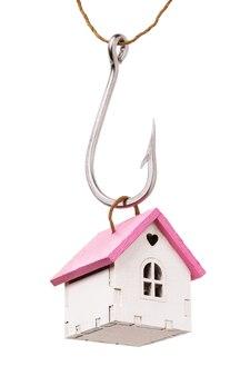 Casa de brinquedo em um gancho isolado em um fundo branco