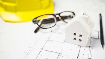 Casa de bugiganga perto de óculos e blueprint